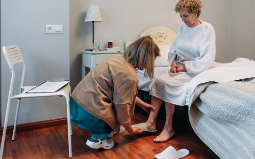 Home care nurse putting slippers on resident